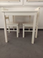 Kindertisch mit zwei weißen Stühlen