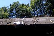 Ausbesserungen am Holzdach eines Gartenhauses