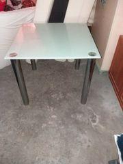 Weißer Glastisch mit Metallfüßen