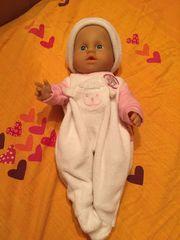 Babypuppe mit Korb und Kleidung