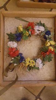 Mehrere Kunstblumen und geflochtenes Herz