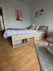 Helles Holzbett mit Stauraum