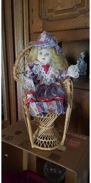 Puppenmädchen im Korbstuhl