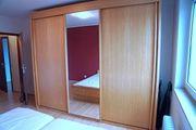 Kleiderschrank mit Schiebetüren und Doppelbett