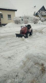rasentraktor mit Schneeschild und Schneeketten