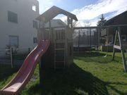 Kinderhaus mit Schaukel und Rutsche