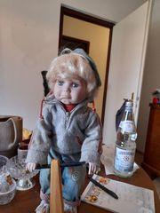 Niedliche Puppenfigur Junge auf Roller
