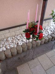Metallkerzenständer mit Kerzen und Kunstblumengesteck