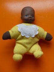 kleine dunkelhäutige Puppe mit gelber