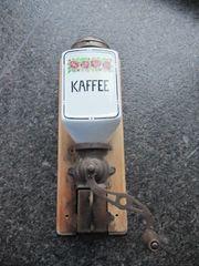 Alte Hand-Kaffeemühle mit Porzellanbehälter Schütte