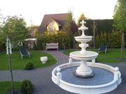 Springbrunnen und Blumenkübel