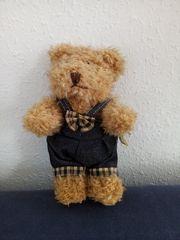 Beiger Teddy-Bär mit blauer Latzhose