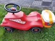 Roter Bobbycar mit Koffer