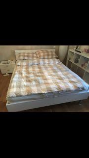 weißes Bett mit Nachtkästchen