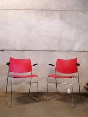 roter Holzstuhl mit schwarzen Armlehnen