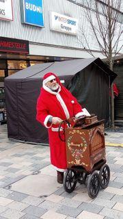 Weihnachtsmann mit Drehorgel für fast