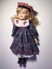 Porzellan Puppe mit roter Mütze