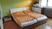 Bett mit Nachtkästchen und Anrichte