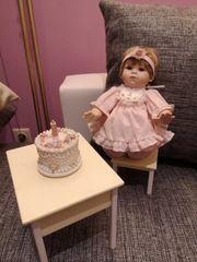 Puppe auf Stuhl mit Tisch