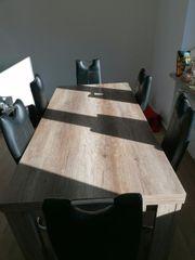 Tisch mit 6 schwarzen Stühlen