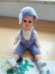 kleine Puppe mit lila Strickkleidung